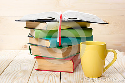 Stack of colorful books, open book and cup on wooden table. Back to school. Copy space Stock Photo