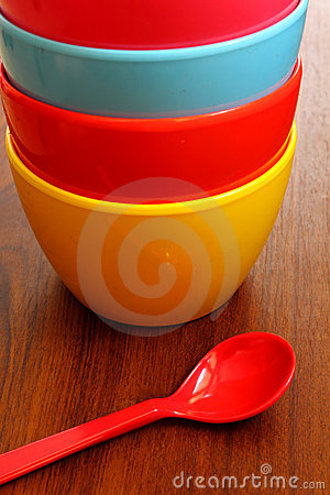 Stack of colorful plastic bowl with blue spoon