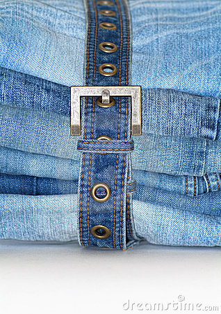 Stack of folded blue jeans with jean belt