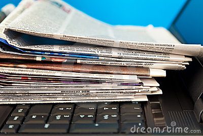Stack of newspapers on laptop