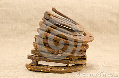 Stack of old retro horse shoes on linen background