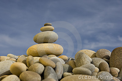 Stack of round peebles with blue sky - zen and spa