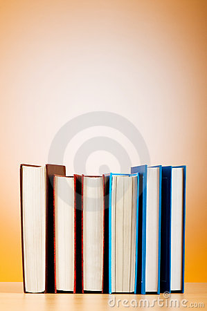 Stack of text books against gradient