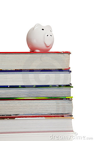 Stack of textbooks with a piggy bank on white