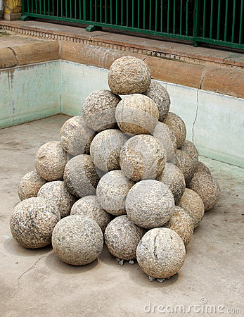 Stacked ancient Canon balls made of granite rock