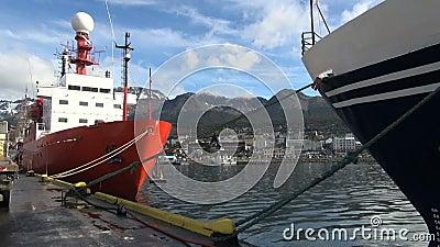 Stad en bergen tussen gedokte schepen stock videobeelden