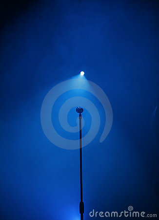 Stage with microphone and blue spotlight