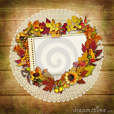 Stamp-frame with autumn leaves on a wooden background
