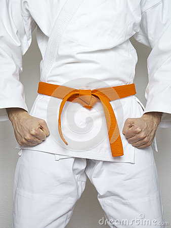 Free Standing Fighter Orange Belt Martial Arts White Suit Stock Photos - 54632053
