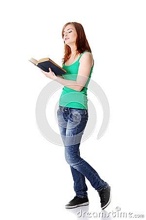 Standing teen girl reading a book.