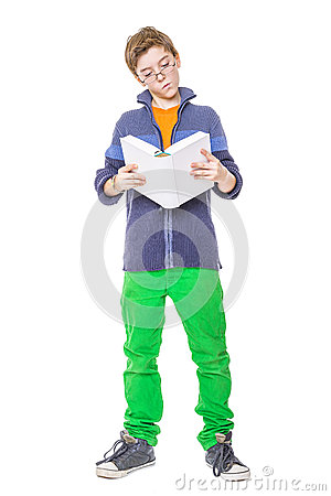Standing teenager with glasses reading a book