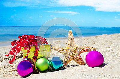 Starfish with gift box and christmas balls on the beach