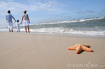 Starfish and tranquil family on the beach