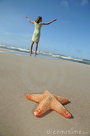 Starfish and tranquil girl on the beach