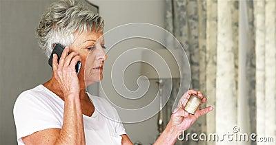 Starsza kobiety mienia pigułki butelka i opowiadać na telefonie komórkowym w sypialni zdjęcie wideo