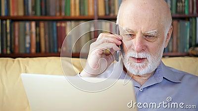 Starszy mężczyzna siedzi w domu z laptopem i smartphone Używać telefon komórkowego dyskutuje projekt na ekranie zbiory
