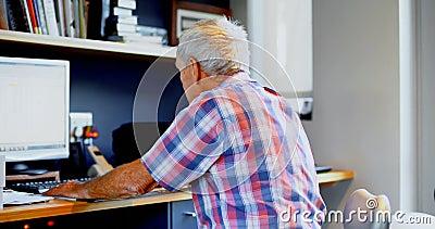 Starszy mężczyzna używa komputer stacjonarnego 4k w domu zdjęcie wideo