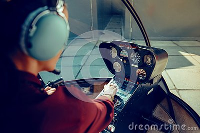 Resolute experienced female pilot observing information on dashboard Stock Photo