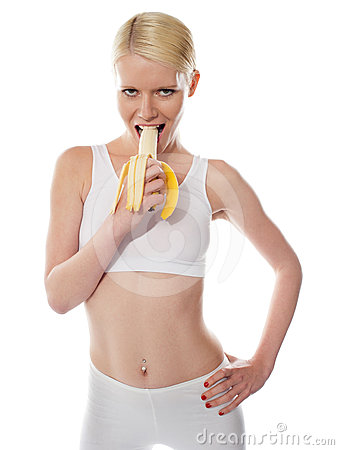 Starving sexy woman eating banana