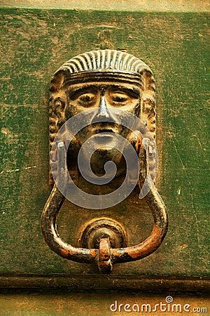 Stary Włoski drzwiowy knocker na zielonym drewnie