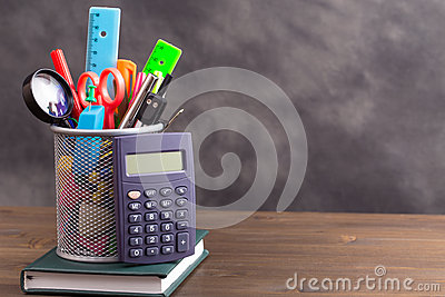 Stationery items with calculator at left side on wooden table