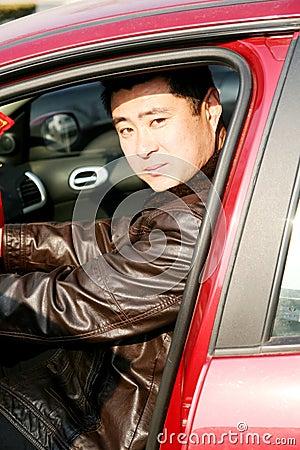 Stattlicher asiatischer Mann im Auto