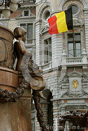 Statue of young boy looking at Belgian flag