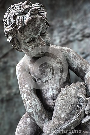 Statue of boy looking at seashell
