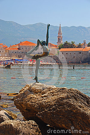 Statue of Naked Dancing Girl on a Rock with Budva Old Town in the Background