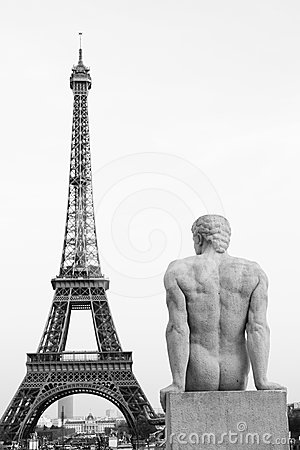 A statue watching the Eiffel Tower Paris