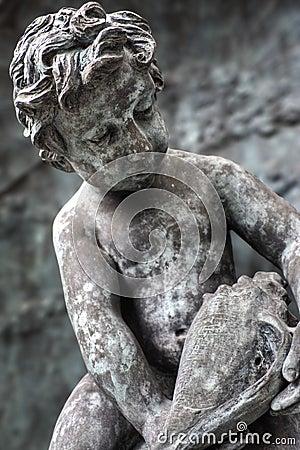 Staty av pojken som ser snäckskal