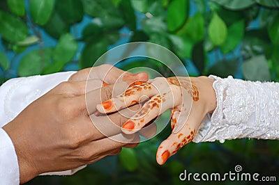 Stawia obrączkę ślubną na palcu