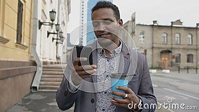 Steadicam tiró de hombre de negocios feliz joven usando smartphone y caminar con la taza de café al aire libre almacen de video