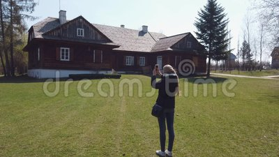 Girl tourist makes a photos of wooden house in an old European village. A steady shot of Girl tourist makes a photos of wooden house in an old European Celtic