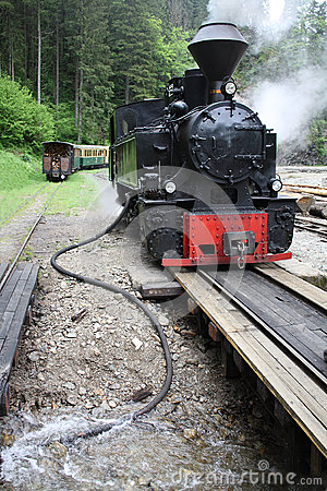 Steam train refilling with water
