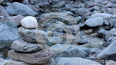 Steensteenhoop naast een rivier stock footage