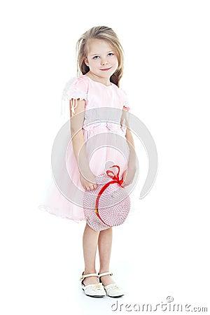 Stehendes kleines blondes mädchen im rosafarbenen kleid mit hut in
