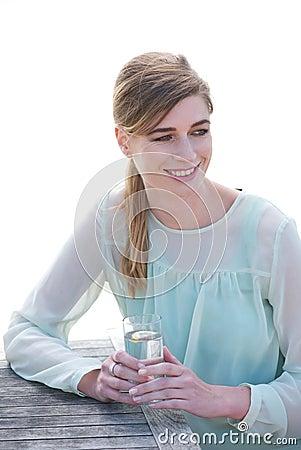Stående av en lycklig ung kvinna som tycker om en drink a