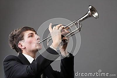 Stående av en ung man som leker hans trumpet