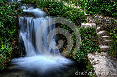 Steps next to a waterfall in green garden