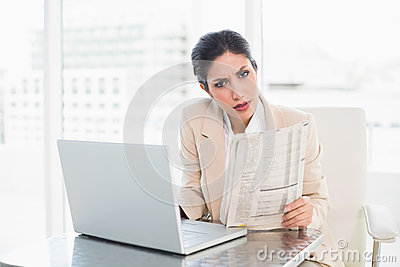 Stern businesswoman holding newspaper while working on laptop lo