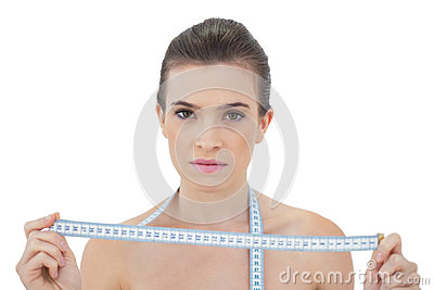 Stern natural brown haired model holding a measuring tape