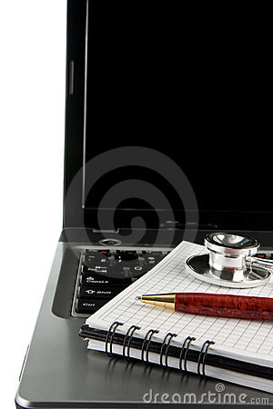 Stethoscope and pen at notebook laptop