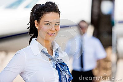 Stewardesses Smiling With Pilot And Private Jet In