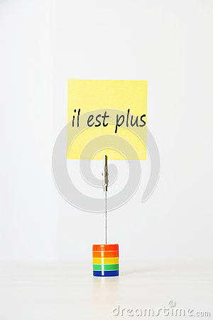 Sticky notepaper with French text il est plus (It s over) clipped to a multicolored card holder