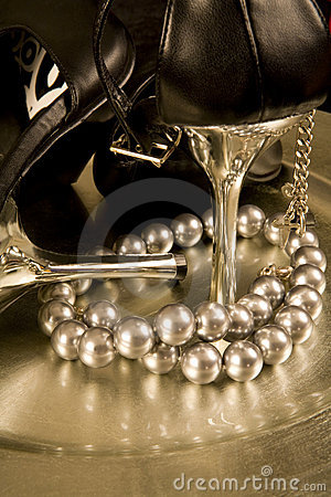 Stilettos and a string of pearls on a tray