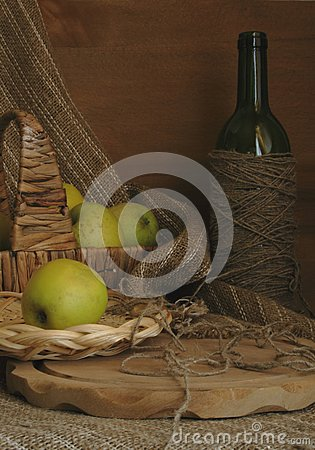 Still-life with apples, a basket and a bottle