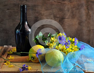 Still life with a bottle by lemons and flowers