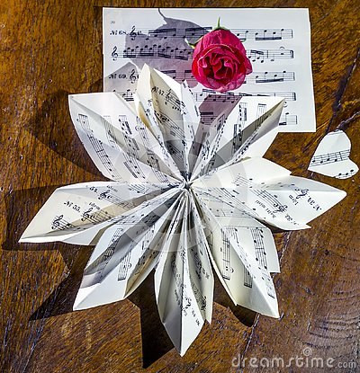 Still life composition made with a musical score folded in the shape of a flower and a red rose Stock Photo