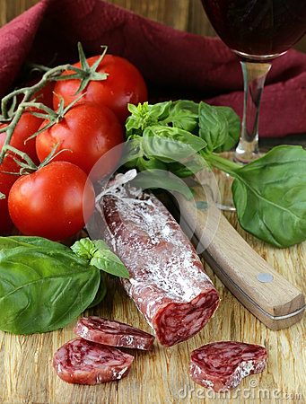 Still life of delicacy salami, tomatoes and basil